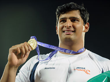 Indian discus throw gold medal winner Vikas Gowda (C) holds up his medal during the presentation ceremony on the second day of the five-day Asian Athletics Championship 2013 at the Chatrapati Shivaji Stadium in Pune on July 4, 2013. AFP PHOTO/Manjunath KIRAN / AFP PHOTO / Manjunath Kiran