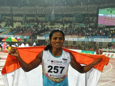 "(FILES) In this photograph taken on July 7, 2017, India's Dutee Chand celebrates after placing third in the women's 100m event at the 22nd Asian Athletics Championships at Kalinga Stadium in Bhubaneswar. Indian sprinter Dutee Chand vowed July 11 to fight any efforts to bar her from the sport, after new research showed runners born with high testosterone levels enjoy a ""significant competitive advantage"". The 21-year-old was banned after being diagnosed in 2014 with hyperandrogenism -- a condition that causes high natural levels of the hormone in women. / AFP PHOTO / Dibyangshu SARKAR"