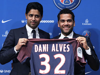 Paris Saint Germain's (PSG) new Brazilian defender Dani Alves (R) and PSG's Qatari president Nasser Al-Khelaifi (R) pose with Alves' jersey during a press conference on July 12, 2017, in Paris. Alves has signed a two-year deal with Paris Saint-Germain, the French club confirmed on July 12. / AFP PHOTO / Thomas Samson