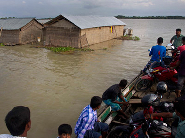 Indians on a boat cross flood waters past partially submerged houses in Burgaon, 80 kilometers from Guwahati. AP