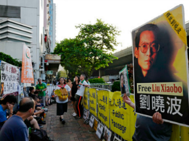 Protesters display pictures of jailed Chinese Nobel Peace laureate Liu Xiaobo. AP