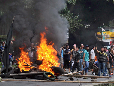 GJM Youth wings members raise slogans after burning articles as they clash with police during Khukrai rally in Sukna, near Siliguri on Saturday. PTI