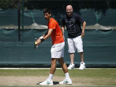Serbia's Novak Djokovic is watched by his coach Andre Agassi as he serves during a practice session ahead of the Wimbledon Tennis Championships in London, Sunday, July 2, 2017. (AP Photo/Alastair Grant)
