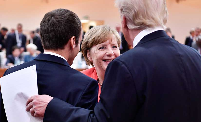 French president Emmanuel Macron, German Chancellor Angela Merkel and US president Donald Trump, from left, are engaged in conversation at the G20 summit in Hamburg. AP