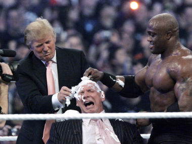 Donald Trump (left) and Bobby Lashley (right) shave the head of Vince McMahon. AP