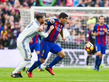 Luis Suarez of Barcelona and Sergio Ramos of Real Madrid vie for the ball. Getty Images