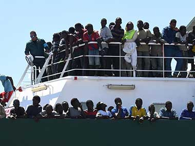 Migrants wait to disembark from the Spanish ship 'Rio Segura' in the harbor of Salerno, Italy. AP
