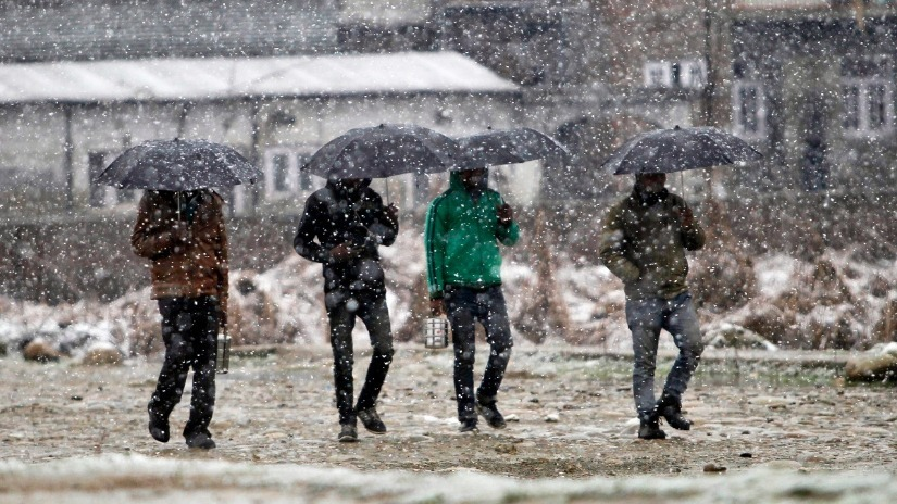 Men hold umbrellas to shield themselves from snow as they walk down a snow-covered street in Narbal on the outskirts of Srinagar. Reuters Image