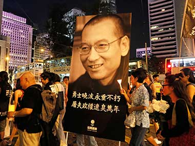 Protesters carry a picture of late Chinese Nobel Peace laureate Liu Xiaobo as they march to mourn Liu at a down town street in Hong Kong. AP