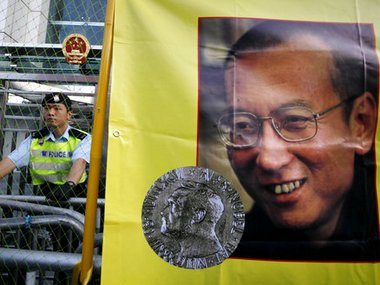A police officer stands guard beside a picture of jailed Chinese dissident Liu Xiaobo. AP