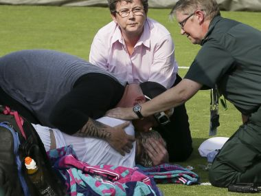 US player Bethanie Mattek-Sands (L floor) is comforted by her husband Justin Sands (L top) as she gets attention from medics on court after suffering an injury during her women's singles second round match against Romania's Sorana Cirstea on the fourth day of the 2017 Wimbledon Championships at The All England Lawn Tennis Club in Wimbledon, southwest London, on July 6, 2017. America's Bethanie Mattek-Sands suffered a horror knee injury at Wimbledon on Thursday which left her screaming and crying in pain in the middle of the court. The 32-year-old collapsed to the ground after damaging her right knee as she approached the net in the first game of the deciding set against Romania's Sorana Cirstea on Court 17. / AFP PHOTO / Daniel LEAL-OLIVAS / RESTRICTED TO EDITORIAL USE