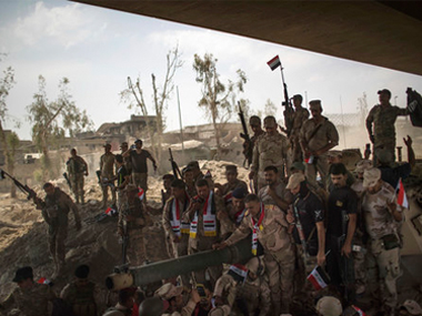 Iraqi Army soldiers gather to celebrate their gains as their fight against Islamic State militants continues in the Old City of Mosul, Iraq, on Sunday. AP