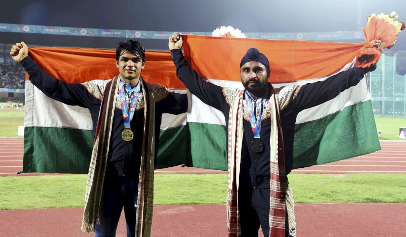 India's gold and silver medal winner javelin throwers Neeraj Chopra (L) and Davinder Singh Kang celebrate during the medal ceremony. PTI