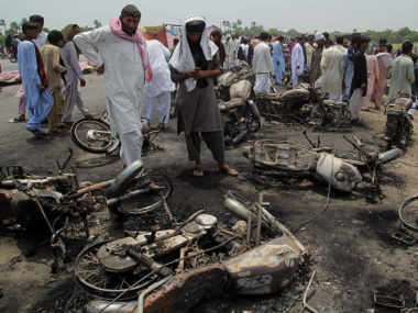 Local residents examine the burnt motorcycles at the site of the oil tanker fire. AP