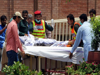 File image of Pakistani rescue worker and hospital staff transporting a victim of oil tanker explosion at a hospital in Multan. AP
