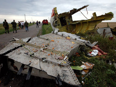 People near parts of the wreckage of the Boeing 777. Reuters