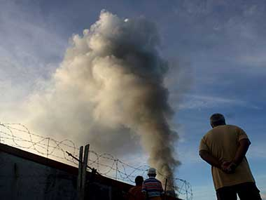 A man looks at a burning structure during early morning airstrikes by government forces in the continuing fight for Marawi city by Islamist militants in southern Philippines. AP