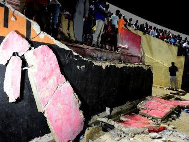 People stand next to a collapsed wall at Demba Diop Stadium on Saturday in Dakar. AFP