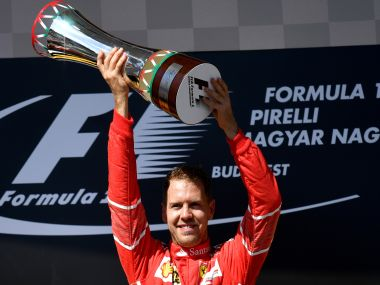Ferrari's German driver Sebastian Vettel celebrates on the podium with his trophy after winning the Formula One Hungarian Grand Prix at the Hungaroring racing circuit in Budapest on July 30, 2017. / AFP PHOTO / ANDREJ ISAKOVIC