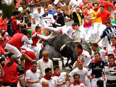 Revellers run as others fall on Miura's fighting bulls during the running of the bulls at the San Fermin Festival, in Pamplona. AP