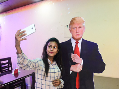 A Bangladeshi customer takes selfie with a cutout US President Donald Trump at the Trump Cafe in Dhaka. Getty Images