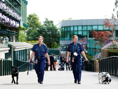 ecurity staff with dogs before the start of play at Wimbledon. Reuters