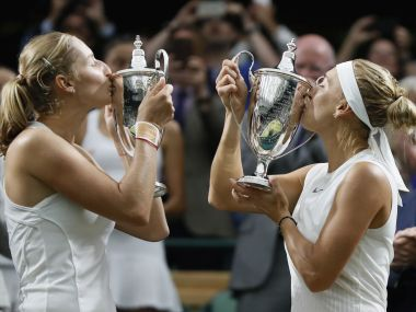 Elena Vesnina of Russia, right and her compatriot Ekaterina Makarova, kiss their winners trophies after they defeated Romania's Monica Niculescu, and Taiwan's Hao-Ching Chan to win the Women's Doubles final match on day twelve at the Wimbledon Tennis Championships in London Saturday, July 15, 2017. (AP Photo/Kirsty Wigglesworth)