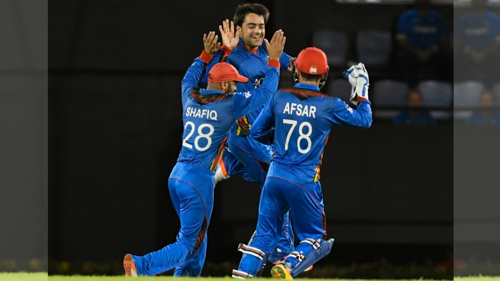 Rashid Khan (C) Shafiqullah Shafaq (L) and Afsar Khan Zazai (R) of Afghanistan celebrate the dismissal of Roston Chase of West Indies during the 1st ODI match between West Indies and Afghanistan at Darren Sammy National Cricket Stadium, Gros Islet, St. Lucia, on 9 June 2017 — AFP PHOTO