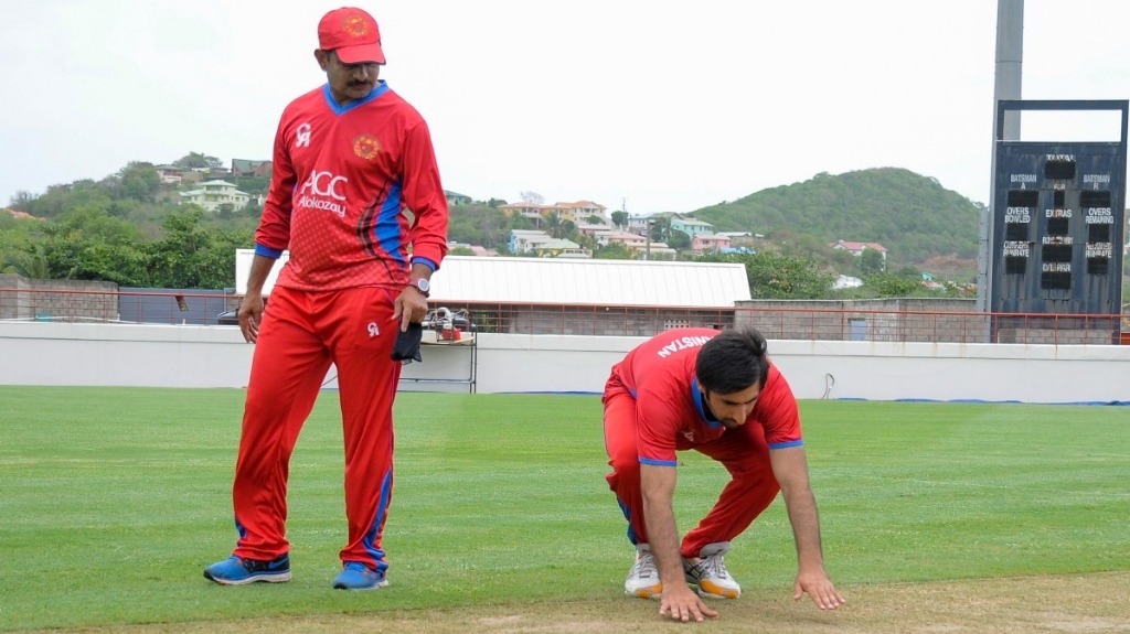 Lalchand Sitaram Rajput of Afghanistan (L) watches as teammate Mohamad Asghar Stanikzai (R) of Afghanistan inspects the pitch during a training session at Darren Sammy National Cricket Stadium on 8 June 2017 in St. Lucia ahead of the West Indies vs Afghanistan ODI game scheduled on 9 June 2017 — AFP PHOTO