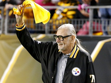 "FILE - In this Oct. 1, 2015, file photo, horror film director George Romero, who directed ""The Night of The Living Dead"" waves a Terrible Towel before an NFL football game between the Pittsburgh Steelers and the Baltimore Ravens in Pittsburgh. It was the anniversary of the film that was made in the Pittsburgh area. Romero, whose classic ""Night of the Living Dead"" and other horror films turned zombie movies into social commentaries and who saw his flesh-devouring undead spawn countless imitators, remakes and homages, has died. He was 77. Romero died Sunday, July 16, 2017, following a battle with lung cancer, said his family in a statement provided by his manager Chris Roe. (AP Photo/Gene J. Puskar, File)"