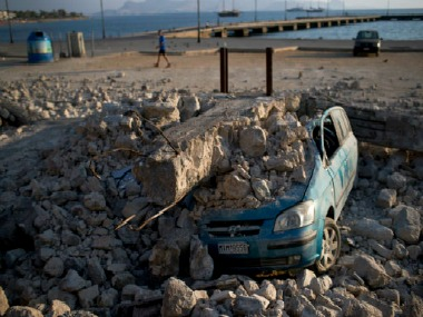 A man walks past a car crushed under rubble near the port of the Greek island of Kos. AP