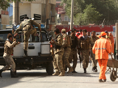 Security forces leave the site of a suicide attack in Kabul. AP