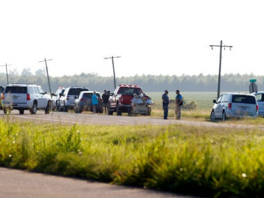 Emergency personnel stand along US Highway 82 after a military transport plane crashed into a field near Itta Bena on Monday. AP