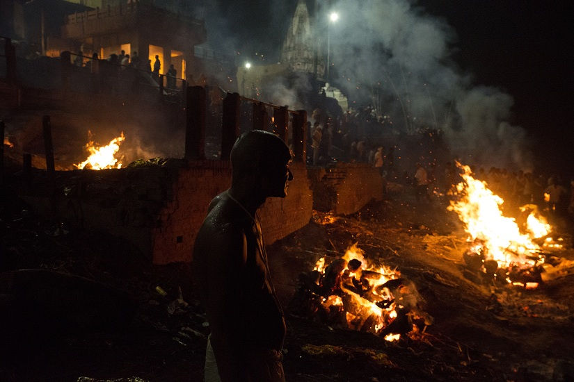 VARANASI, UTTAR PRADESH, INDIA - 2016/06/26: A man looks on as corpses are being cremated at night at Manikarnika ghat in Varanasi. It is a traditional holy place on the banks of river Ganges to cremate dead bodies of the Hindus. Hindu mythology teaches that the ghat is especially sacred because people cremated there receive moksha (salvation). Varanasi is a holy town for the Hindus where numerous religious take place centering the Ganges throughout the year. It is also considered the oldest living town in the world. (Photo by Subhendu Sarkar/LightRocket via Getty Images)