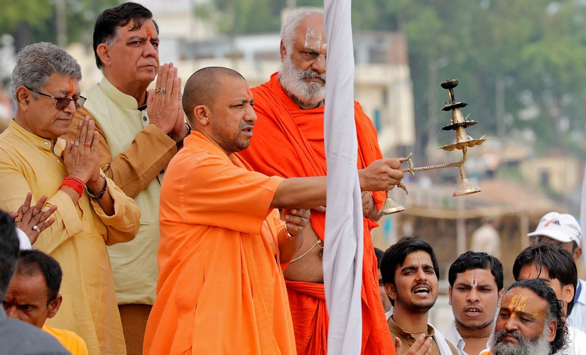 """Yogi Adityanath, Chief Minister of India's most populous state of Uttar Pradesh, holds a traditional lamp as he performs prayers called """"Aarti"""" on the banks of river Sarayu in Ayodhya, India, May 31, 2017. REUTERS/Pawan Kumar - RTX38BJC"""