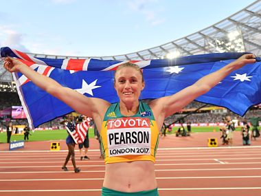Australia's Sally Pearson celebrates with her national flag after winning the final of the women's 100m hurdles athletics event at the 2017 IAAF World Championships at the London Stadium in London on August 12, 2017. / AFP PHOTO / Ben STANSALL