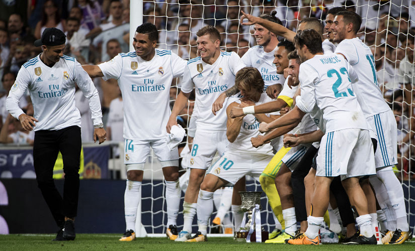 Real Madrid's players joke with Cristiano Ronaldo as they celebrate their Supercup victory against FC Barcelona at the Santiago Bernabeu stadium in Madrid. AFP