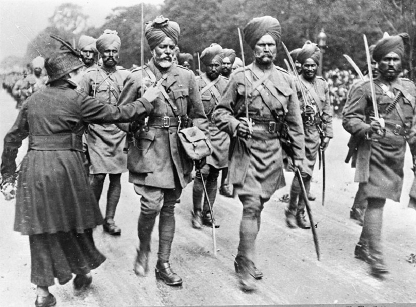 A woman pins a flower to an Indian soldier during a march-past, 1914. Photo credit: Imperial War Museum