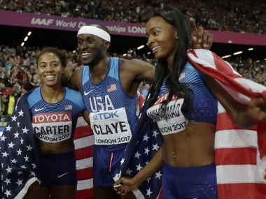 United States' triple jump silver medal winner Will Claye, center, celebrates with women's 400-meter hurdles gold medal winner United States' Kori Carter, left, and United States' silver medal winner Dalilah Muhammad, right, during the World Athletics Championships in London Thursday, Aug. 10, 2017. (AP Photo/Matt Dunham)