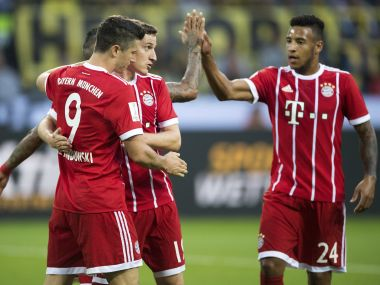 Bayern's Robert Lewandowski, left celebrates with teammates Sebastian Rudy, center, and Corentin Tolisso after scoring during the Supercup soccer final between FC Bayern Munich and Borussia Dortmund in the Signal-Iduna-Park in Dortmund, Germany, Saturday, Aug. 5 2017. (Marius Becker/dpa via AP)
