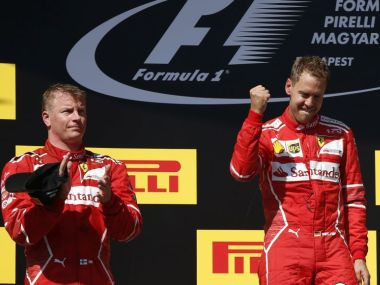Second placed Ferrari driver Kimi Raikkonen of Finland' left, applauds as teammate Sebastian Vettel of Germany celebrates after winning the Hungarian Formula One Grand Prix, at the Hungaroring racetrack in Mogyorod, northeast of Budapest, Sunday, July 30, 2017. (AP Photo/Darko Bandic)