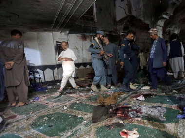 Policemen and relatives inspect the site of the suicide attack. Reuters