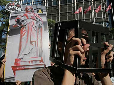 Protesters wearing the uniform of prisoners and raise a poster with an image of Statue of the Goddess of Justice during a rally to support young activists Joshua Wong, Nathan Law and Alex Chow in downtown Hong Kong on Sunday. AP
