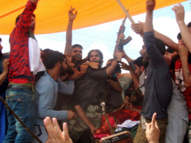 A militant offers gun-salute at the funeral of Suhail Ahmad Tantray in a village in Kulgam. Image courtesy: Hilal Shah