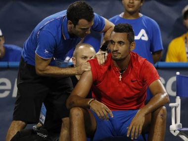 Aug 2, 2017; Washington, DC, USA; Nick Kyrgios of Australia receives treatment from an ATP trainer during an injury timeout against Tennys Sandgren of the United States (not pictured) on day three of the Citi Open at Fitzgerald Tennis Center. Sandgren won 6-3, 3-0 (Ret'd). Mandatory Credit: Geoff Burke-USA TODAY Sports - RTS1A6QH