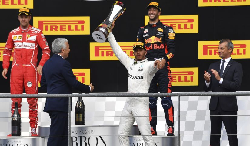 Mercedes driver Lewis Hamilton, center, jubilates while raising his trophy on the podium after winning the Belgian Grand Prix. Ferrari driver Sebastian Vettel, left, placed second and Red Bull driver Daniel Ricciardo, second right, placed third. AP