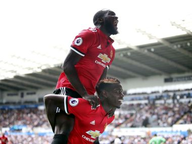 Manchester United's Paul Pogba on ground, celebrates scoring his side's third goal with team-mate Romelu Lukaku, during the English Premier League soccer match between Swansea and Manchester United, at the Liberty Stadium, in Swansea, Wales, Saturday Aug. 19, 2017. (Nick Potts/ PA via AP)