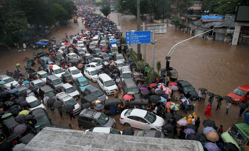 Vehicles stuck at a flooded street after heavy rains at Thane in Mumbai on Tuesday. PTI