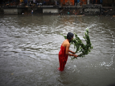A Nepali woman lashes herself with the leaves of an Aghada herb as part of a ritual to wash away sins committed during menstruation period. AP