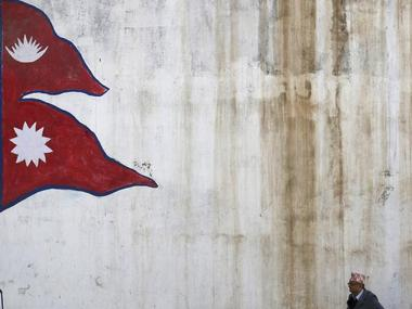 A man stands near a wall with a painting of a Nepali national flag as he waits for a bus in Kathmandu, Nepal October 16, 2015.   REUTERS/Navesh Chitrakar